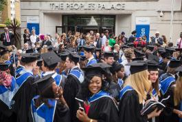 A crowd of students in graduation gowns and caps, outside The People's Palace building at the Mile End campus of Queen Mary University of London